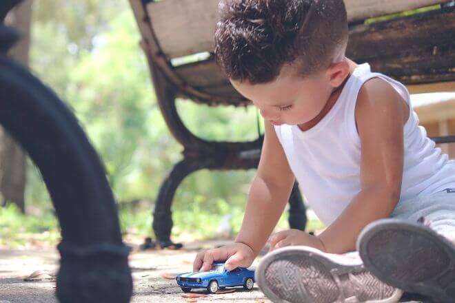 Chłopiec bawiący się zabawkowym samochodzikiem