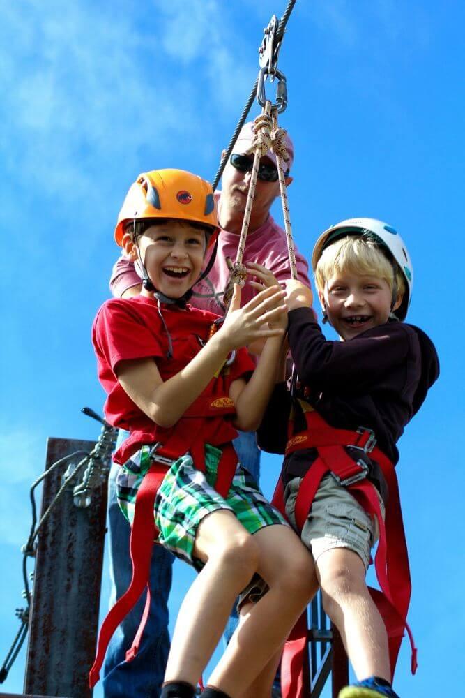 dzieci zjeżdżające na kolejce tyrolskiej