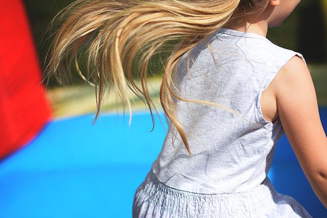 dziecko bawiące się na trampolinie
