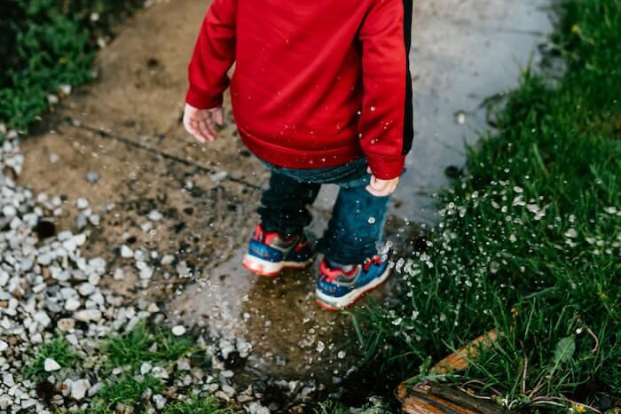 Chłopiec bawiący się w deszczu
