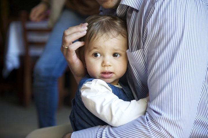 Dziecko siedzące na kolonach u taty