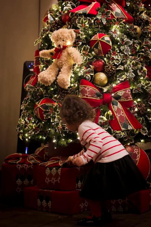 Dziewczynka wyciągająca prezent spod choinki