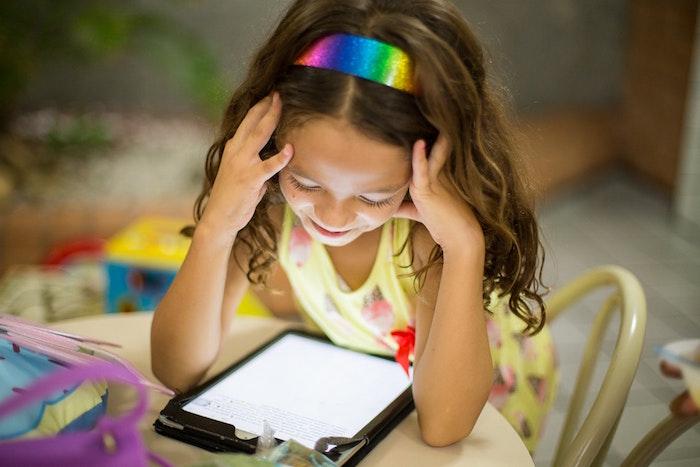 Dziewczynka patrząca w ekran tabletu