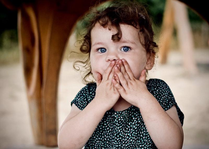 dziewczynka zakrywająca rękami usta