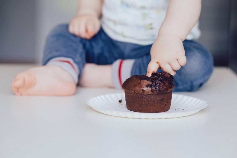 dziecko z czekoladową babeczką