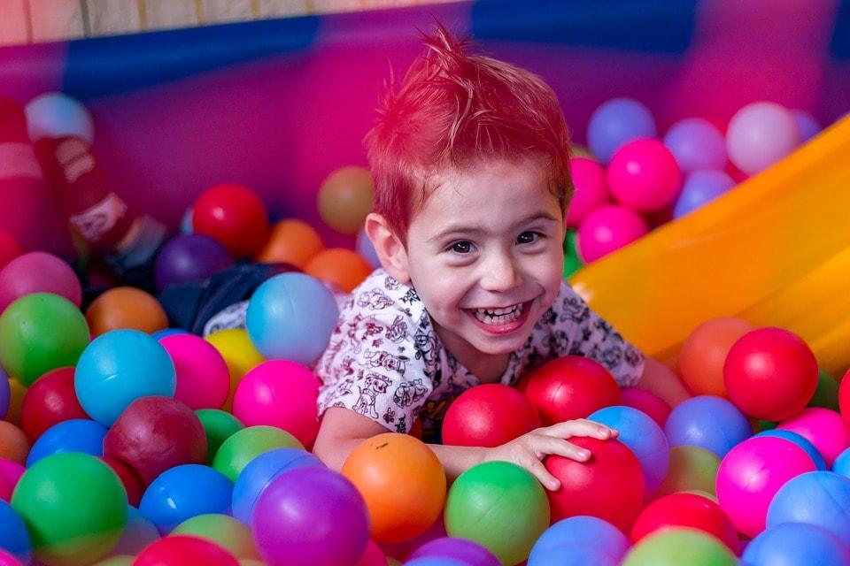 Chłopczyk bawiący się w basenie z piłkami