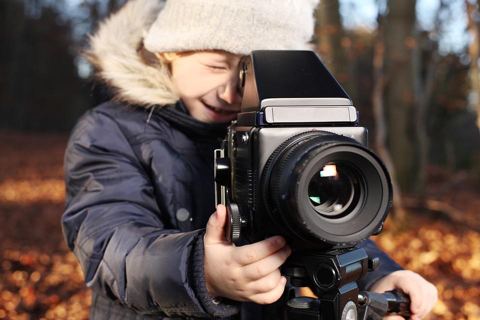 Dziecko uczące się obsługi kamery filmowej